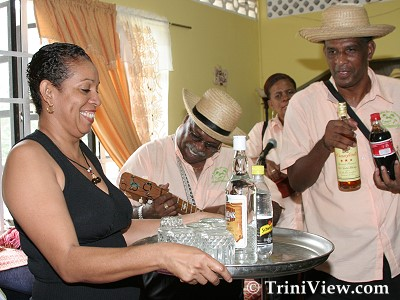 Member of the Cornelio family serves drinks to commerorate the festive occasion